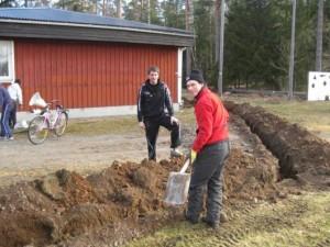 """Två viktiga kuggar - Johan och nyförvärvet Robert - lägger kabel i diket som """"Trälsmo"""" grävt."""